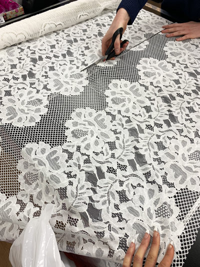 cutting white lace fabric
